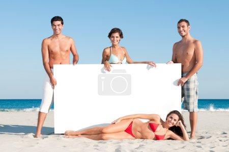 Foto de Feliz grupo sonriente de amigos sosteniendo un tablero blanco para el texto en la playa de verano - Imagen libre de derechos