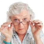 Happy surprised old senior lady looking through he...