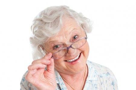 Photo pour Joyeux sourire dame à la retraite portant sa nouvelle paire de lunettes isolées sur fond blanc - image libre de droit