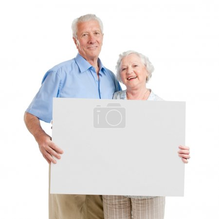 Photo for Smiling aged retired couple holding together a white board isolated on white background - Royalty Free Image