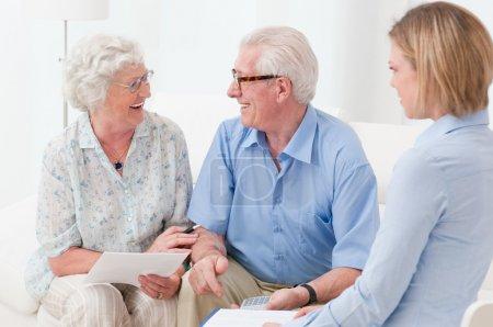 Photo pour Joyeux couple de personnes âgées scellant avec une poignée de main un contrat pour la retraite - image libre de droit