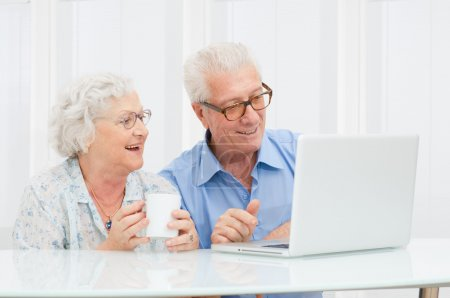 Photo for Happy smiling retired couple using computer laptop at home - Royalty Free Image