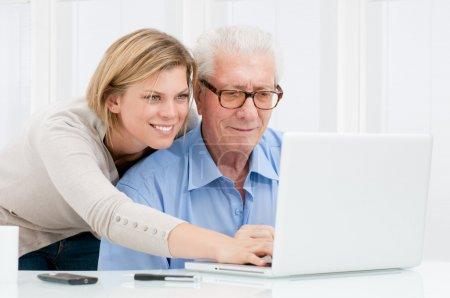 Photo pour Heureuse jeune fille souriante enseignement et montrant la nouvelle technologie informatique à son grand-père - image libre de droit
