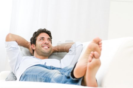 Photo for Smiling young man relaxing and dreaming on sofa at home - Royalty Free Image