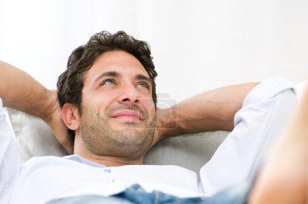 Photo pour Sereine détente sur le canapé à la maison heureux homme - image libre de droit