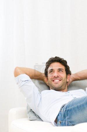 Photo pour Jeune homme souriant rêvant de son avenir et se relaxant sur le canapé à la maison - image libre de droit
