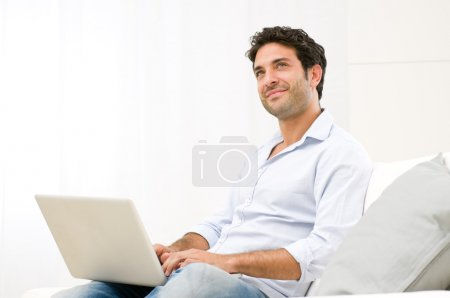 Photo for Smiling dreaming young man looking up while working at laptop computer - Royalty Free Image