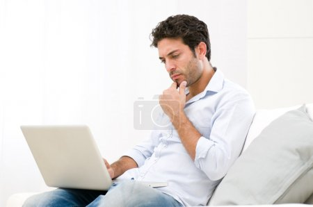Pensive worried guy at laptop