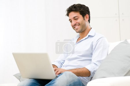 Photo for Happy smiling young man watching and working on computer laptop at home - Royalty Free Image