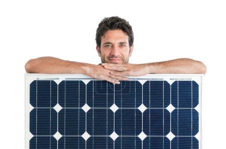 Foto de Hombre demuestra sonriendo y sosteniendo un panel solar aislado sobre fondo blanco - Imagen libre de derechos