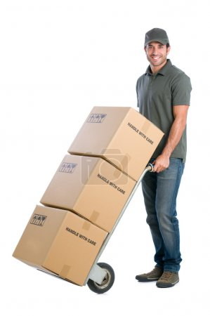 Photo for Smiling young delivery man moving boxes with dolly, isolated on white background - Royalty Free Image
