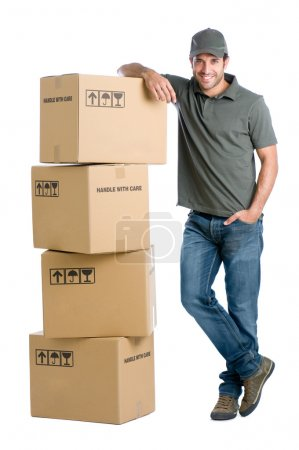 Photo for Satisfied and proud delivery man leaning on a stack of boxes isolated on white background - Royalty Free Image