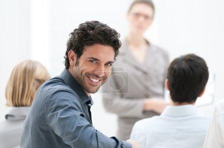 Photo pour Satisfait homme d'affaires regardant la caméra lors d'une conférence d'affaires - image libre de droit