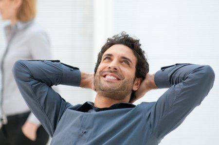 Photo pour Heureux homme d'affaires souriant levant avec rêve expression au bureau - image libre de droit