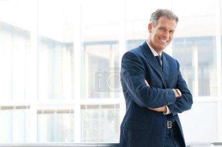 Photo for Happy mature business man looking at camera with satisfaction at office - Royalty Free Image