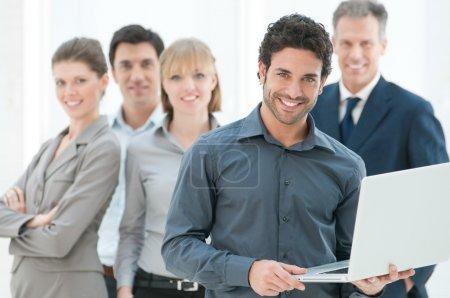 Photo pour Homme d'affaires heureux maintenant un ordinateur portable moderne avec son équipe en arrière-plan - image libre de droit