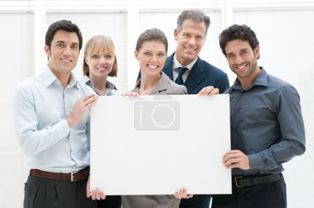 Photo for Happy smiling business team holding a blank placard ready for your text or product - Royalty Free Image