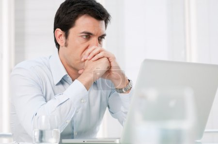 Photo for Pensive absorbed business man watching at computer laptop with worried expression - Royalty Free Image