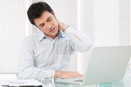 Photo for Businessman with neck pain after long hours at work - Royalty Free Image
