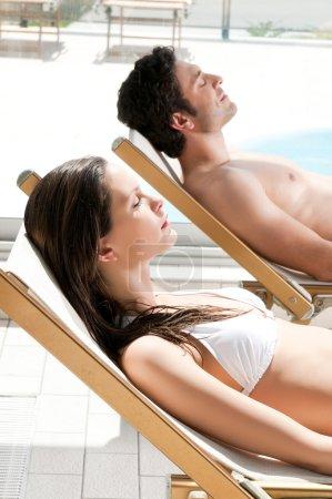 Photo pour Couple détendu bronzer ensemble à la piscine en été - image libre de droit