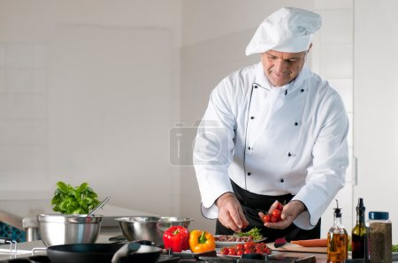 Photo for Happy smiling mature chef preparing a meal with various vegetables - Royalty Free Image