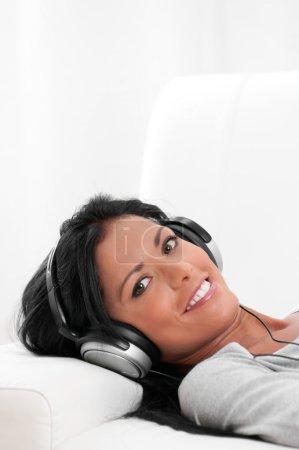 Photo pour Belle fille latine écouter de la musique tout en étant allongé sur le canapé à la maison - image libre de droit