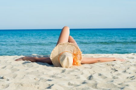 Photo for Young Woman Enjoying Sunbath On White Beach - Royalty Free Image