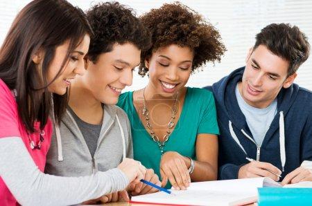 Photo pour Joyeux groupe de jeunes étudiants étudient ensemble dans la bibliothèque - image libre de droit