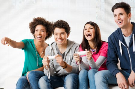 Photo for Happy Group Of Young Friends Playing Video Games At Hom - Royalty Free Image