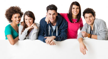 Happy multi ethnic group of friends showing blank billboard
