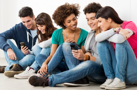 Photo for Group Of Happy Young Friends Looking At Cell Phon - Royalty Free Image