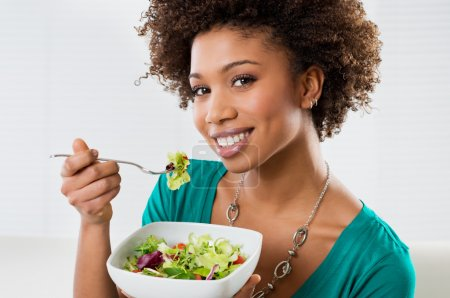Photo for Close-up Of Beautiful African American Woman Eating Salad At Hom - Royalty Free Image