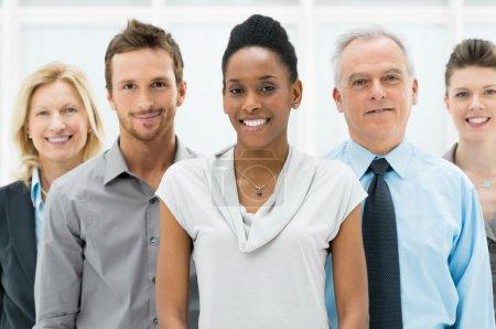 Photo pour Bonne équipe souriante multi ethnique d'affaires au bureau - image libre de droit