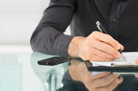 Photo for Businessman examines a contract and writing on paper - Royalty Free Image