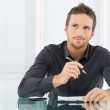 Young Businessman Thinking and Wondering While Wri...