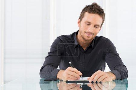 Photo pour Portrait d'homme d'affaires, une paperasserie au bureau d'écriture - image libre de droit