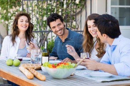 Photo pour Groupe d'amis heureux qui dînent au patio - image libre de droit
