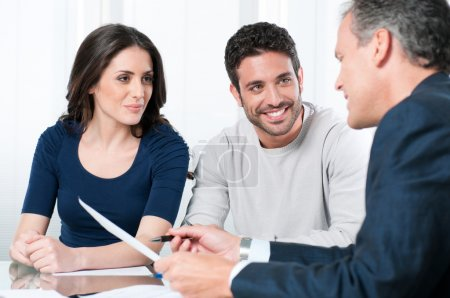 Photo for Financial consultant presents bank investments to a young couple - Royalty Free Image