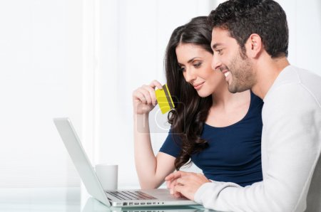 Photo for Smiling satisfied couple buying online with credit card at home - Royalty Free Image