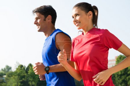 Photo for Young Healthy Couple Jogging At Park In Early Mornin - Royalty Free Image