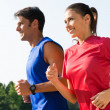 Young Healthy Couple Jogging At Park In Early Morn...