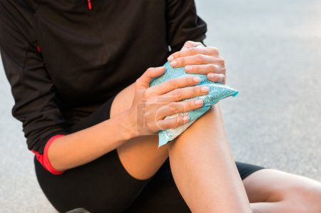 Photo for Female Athlete Sitting On Ground And Taking Treatment For Knee Pain - Royalty Free Image