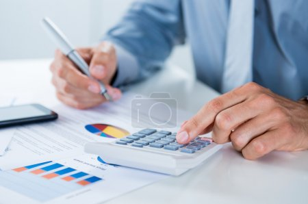 Photo for Close Up Of A Businessman With Documents At Desk Doing Calculations - Royalty Free Image