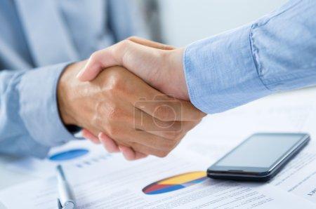 Foto de Primer plano de los empresarios estrechando las manos en el escritorio - Imagen libre de derechos