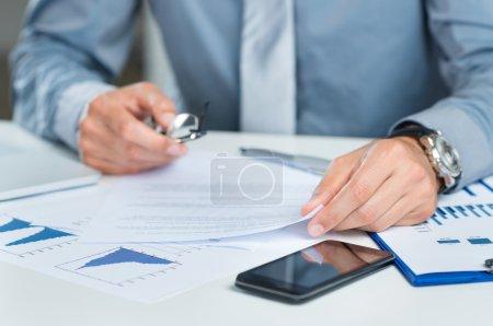 Photo pour Gros plan d'un homme d'affaires avec les documents de travail à son bureau - image libre de droit