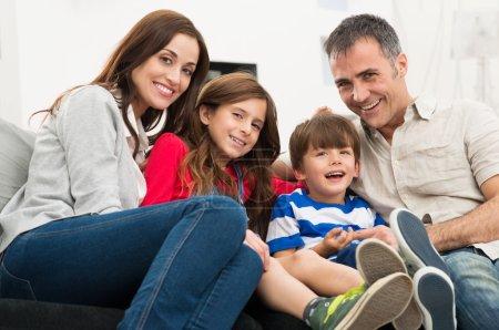 Photo pour Portrait d'une famille souriante heureuse assise sur le canapé - image libre de droit