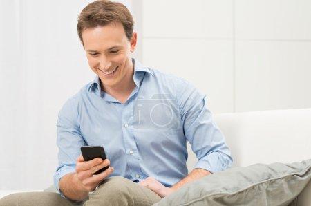 Photo pour Heureux jeune homme assis sur le canapé en lui envoyant le texte sur téléphone portable - image libre de droit