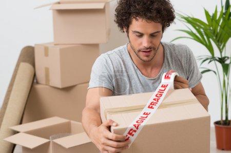 Young Man Packing Cardboard Box