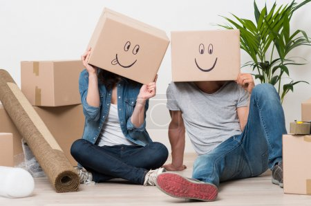 Photo for Couple With Cardboard Boxes On Their Heads With Smiley Face Sitting On Floor After The Moving House - Royalty Free Image