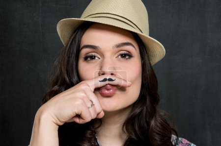 Photo pour Portrait de jeune femme en chapeau avec moustache peinte sur fond gris - image libre de droit
